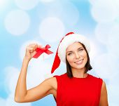 christmas, holidays, winter, happiness and people concept - smiling woman in santa helper hat with jingle bells over blue lights background