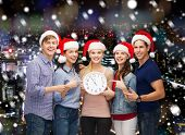 christmas, winter, holidays, time and people concept - group of smiling teenagers in santa helper hats with clock pointing finger over snowy night city background