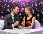 celebration, christmas, holidays and people concept - smiling couple clinking glasses of red wine at restaurant over night lights background