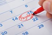 Hand Marking Payday On Calendar