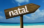 Natal, Brazil wooden sign with a beach on background
