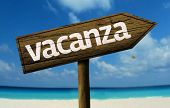 Vacanza - Vacation in Italian - wooden sign with a beach on background
