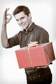 Holiday. Man Giving Red Gift Box Showing Thumb Up