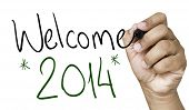 Welcome 2014 hand writing with a black mark on a transparent board