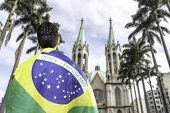 Brazilian holding a brazilian flag looks to Se Cathedral in Sao Paulo, Brazil