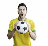 stock photo of patriot  - Brazilian man holding a soccer ball celebrates on white background - JPG