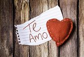 Te Amo written on a peace of paper and a heart on a wooden background