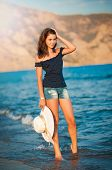 Beautiful teen girl goes on coast of ocean with straw hat in hands .Lady going on the beach