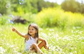stock photo of have sweet dreams  - Little girl having fun in summer day soap bubbles - JPG