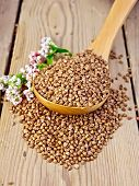 stock photo of buckwheat  - Buckwheat in a wooden spoon with flower buckwheat on a wooden boards background - JPG
