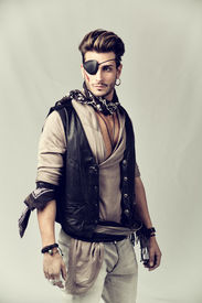 stock photo of pirates  - Good Looking Young Man in Pirate Fashion Outfit on Gray Background - JPG