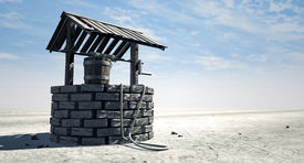 picture of unsafe  - A brick water well with a wooden roof and bucket attached to a rope in a flat barren landscape with a blue sky background - JPG