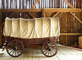 Covered wagon in a sunlit rustic barn