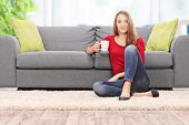 stock photo of early 20s  - Young woman drinking coffee seated by a sofa at home  - JPG