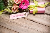 stock photo of i love you mom  - Bunch of flowers and tag with text on wooden background - JPG