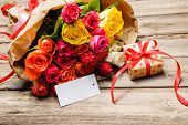 pic of bunch roses  - Bunch of roses and gift box with an empty tag on wooden background - JPG