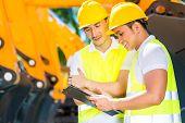 stock photo of machinery  - Asian engineer controlling construction machinery of construction site or mining company - JPG