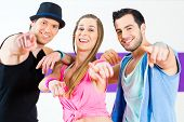 stock photo of zumba  - Group of men and women dancing zumba fitness choreography in dance school - JPG
