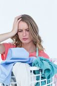 stock photo of dirty-laundry  - Woman looking at dirty clothes on white background - JPG