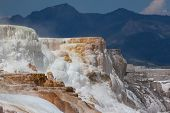foto of mammoth  - Colorful Mammoth Hot Springs cascading down a mountain side with steam rising and mountain landscape background at Yellowstone National Park - JPG