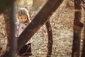 pic of child missing  - Little girl stands among the trees and with a sad expression on her face looking down - JPG