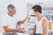 picture of herniated disc  - Doctor showing anatomical spine to his patient in medical office - JPG
