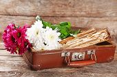 pic of old suitcase  - Old wooden suitcase with old books and flowers on wooden background - JPG