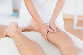 pic of physiotherapist  - Physiotherapist doing calf massage to her patient in medical office - JPG