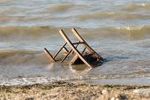 pic of polluted  - Polluted beach with a chair wheel in it - JPG
