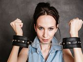 stock photo of handcuff  - Arrest and jail. Criminal woman prisoner girl showing leather handcuffs on gray. Punishment. ** Note: Soft Focus at 100%, best at smaller sizes - JPG