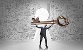 stock photo of keyhole  - Young businessman and keyhole at background lifting big key above head - JPG