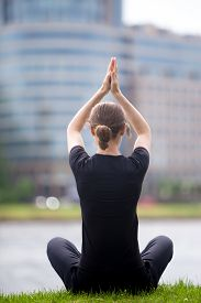 foto of pranayama  - Young business woman sitting cross legged on street in front of blue glass modern office building practicing yoga Easy Pose Sukhasana meditation pranayama breathing full length back view - JPG