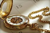picture of watch  - Close up of a gold pocket watch on a calendar in sunlight - JPG