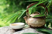 Teapot and cups on stone with bamboo leaves.