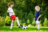 Two Cute Little Sisters Having Fun Playing A Soccer Game poster