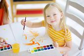 Cute Little Girl Drawing With Colorful Paints At A Daycare poster