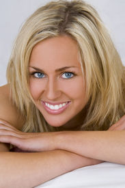 stock photo of blonde woman  - A stunningly beautiful young blond woman with bright blue eyes looking relaxed and happy - JPG