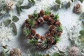 Christmas and New Year holidays concept with snowy fir branches and pine cone wreath on light backgr poster