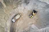 Big Heavy Wheel Loader Loading Sand Into Dump Truck In Sand Pit. Heavy Industrial Machinery Concept poster