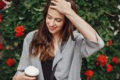 Stylish Hipster Girl With Beautiful Hair Holding Coffee Cup And Smiling In City Street On Background poster