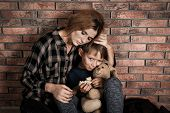Poor Woman Hugging Her Son Near Brick Wall poster