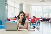 Attractive Young Asian Female College Student Smiling At Camera While Sitting In Library With Laptop poster