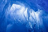 blue ice cave covered with snow and flooded with light
