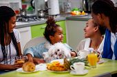 Family breakfast. Young parents with their daughters breakfast at home poster