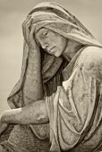 Old statue of a suffering woman with a vintage sepia look