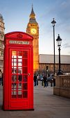 Traditional red phone booth in London with the Big Ben in the background near sunset