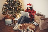 Happy Girl In Santa Hat Working On Laptop And Sitting With Cute Dog At Golden Beautiful Christmas Tr poster
