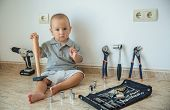 Little Boy Surrounded By Construction Tools. The Child Sits On The Floor With A Construction Tool In poster
