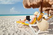 stock photo of yucatan  - Woman with laptop relaxing on the deckchair at the Caribbean sea - JPG