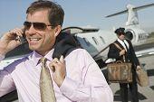Middle aged Geschäftsmann mit Handy, mit Fahrer, die Abhaltung von Gepäck im Hintergrund auf dem Flugplatz
